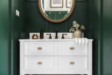 a moody green mudroom in modern farmhouse style, with a white vanity and a mirror in a refined and chic frame