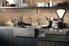 a moody industrial kitchen with black beadboard cabinets, grey stone countertops and rough wooden beam wall and a backsplash