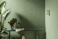 a natural green bathroom with long tiles in a pretty pattern, a green bench and lots of potted plants