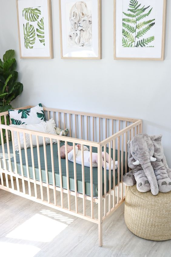 a neutral and modern tropical nursery with fun tropical artworks, potted greenery, tropical leaf pillows and a toy elephant