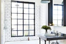 a neutral bathroom with industrial touches – a wood and metal vanity, a metal pendant lamp and a black frame window