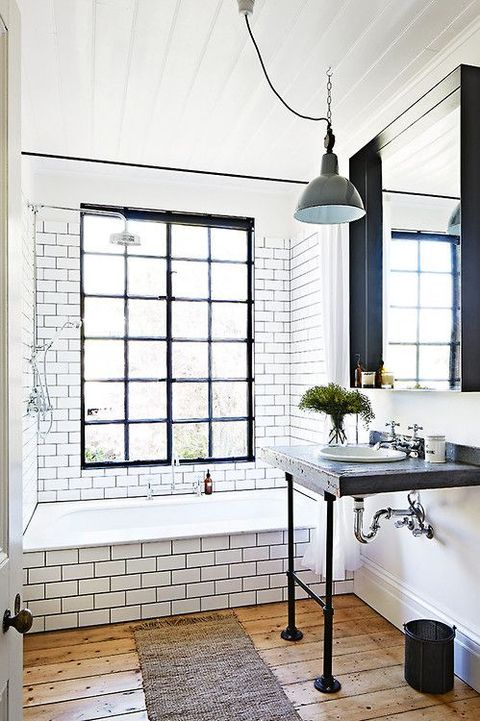 a neutral bathroom with industrial touches   a wood and metal vanity, a metal pendant lamp and a black frame window