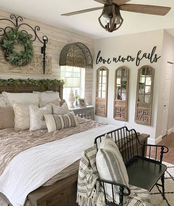 a neutral farmhouse bedroom with a whitewashed wooden wall, vintage wooden furniture, a gallery wall of mirrors and some greenery