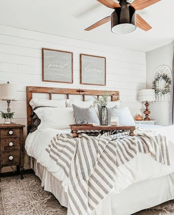 a neutral farmhouse bedroom with shabby wooden furniture, neutral and printed textiles, greenery and cool rustic lamps