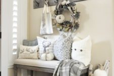 a neutral farmhouse entry with a large sign, a box with pumpkins, printed pillows, a pinecone and pumpkin wreath and a plaid blanket