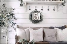 a neutral farmhouse entry with a sign, greenery, potted plants, a wooden bench with neutral textiles