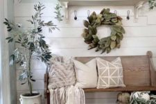 a neutral farmhouse entryway with a leaf wreath, a potted tree, faux pumpkins, candles and neutral textiles