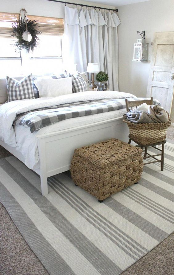 a neutral farmhouse space with a white bed, neutral bedding and buffalo check, baskets for storage and shades and curtains