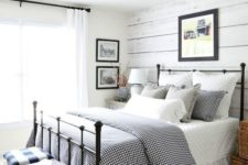 a neutral farmhouse space with a whitewashed wall, a forged bed, buffalo check stools and artworks