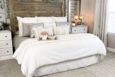 a neutral farmhouse space with an extended headboard, white furniture, some cozy bedding and a rug
