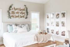a neutral farmhouse space with an upholstered bed, a sign on the wall, a vintage chandelier, a wooden bench and a gallery wall
