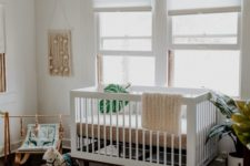 a neutral tropical nursery with boho decor and furniture, monstera leaf print items and potted plants