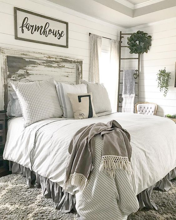 a neutral vintage farmhouse bedroom with white walls, a shabby chic bed, greenery and signs on the walls
