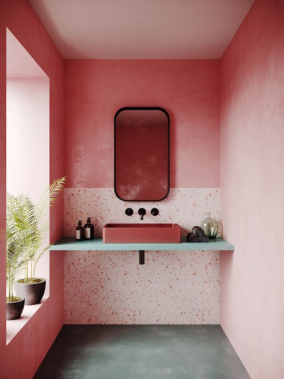 a pink bathroom with bright walls, terrazzo elements, a pink sink and black touches for some drama