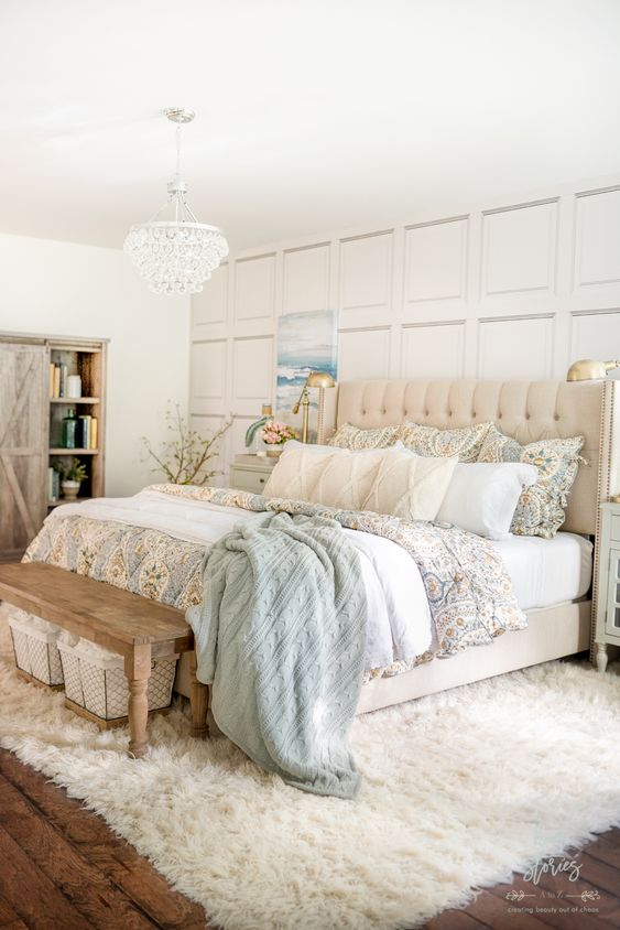 a pretty coastal farmhouse bedroom with a paneled wall, an upholstered bed, a wooden bench, a chic chandelier and a a fux rug