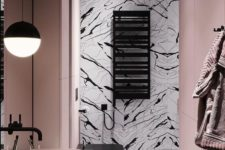 a quirky bathroom with blush walls and a sink, black and white tiles plus black fixtures for an ultra-modern look