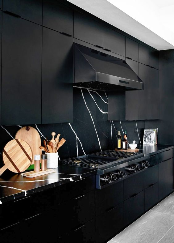 a refined black kitchen with metal cabinets, a marble backsplash and countertops and a black hood