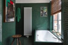 a refined dark green bathroom all clad with tiles including the tub, a modern chandelier, a wooden stool and some pretty artworks