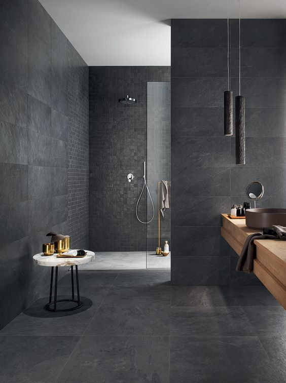 a refined graphite grey bathroom clad with various tiles, with pendant lamps, a wooden vanity and a marble mini table