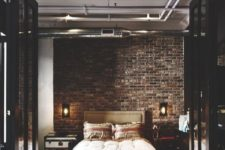 a refined industrial bedroom with brick walls, an upholstered bed, a chest and a dresser and exposed pipes on the ceiling