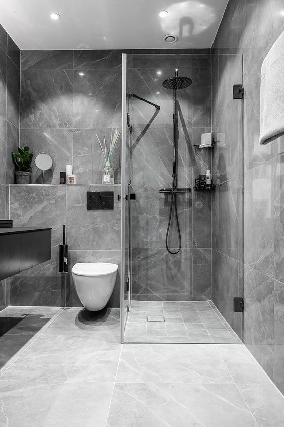 a refined minimalist bathroom clad with a grey marble tiles, with a glass enclosed shower and a black floating vanity