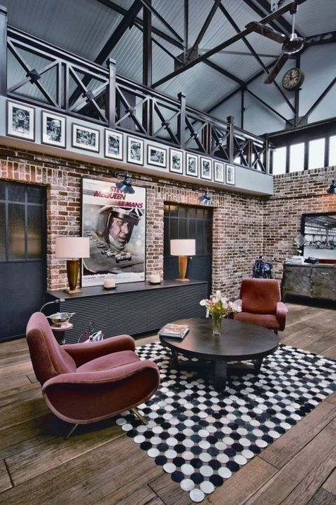 a retro industrial living room with red brick walls, a printed rug, retro furniture and some blooms for a chic look