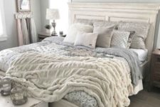 a romantic farmhouse bedroom in dove grey, with vintage white furniture, a shelf over the bed and catchy bedding plus a fur blanket