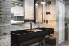 a rough industrial bathroom clad with white bricks, a black stone vanity and black vintage lamps and mirrors