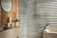 a rustic industrial bathroom with a reclaimed wooden ceiling and wall, corrugated steel walls, a concrete bathtub and sink on metal legs