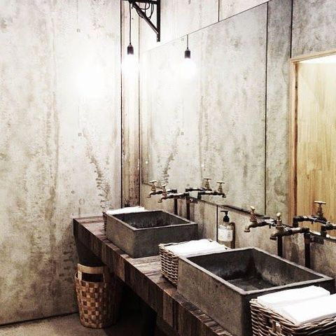 a rustic industrial bathroom with concrete walls, concrete sinks, a wooden vanity and vintage fixtures