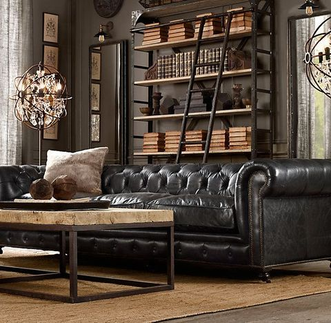 a rustic industrial living room with chic metal shelving units, a catchy chandelier, a leather sofa and a wood and metal table
