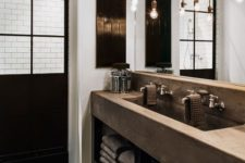 a rustic industrial space with a concrete vanity, a reclaimed wooden floor, bulbs hanging from an exposed pipe over the vanity
