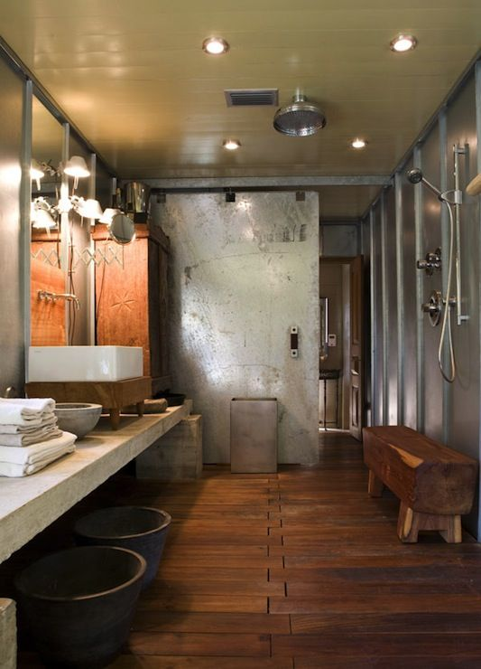 a rustic industrial vanity with a metal sliding door, a wooden floor, a wooden bench, some wooden furniture and a concrete vanity