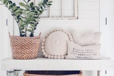 a serene modern farmhouse entryway with a white bench, a vintage window frame, a potted plant and some pillows