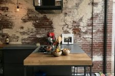 a shabby industrial kitchen with rusty brick walls, black metal cabinets and kitchen island and exposed pipes