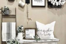 a simple farmhouse entry with a gallery wall, a cotton wreath, potted greenery and a pillow on the bench
