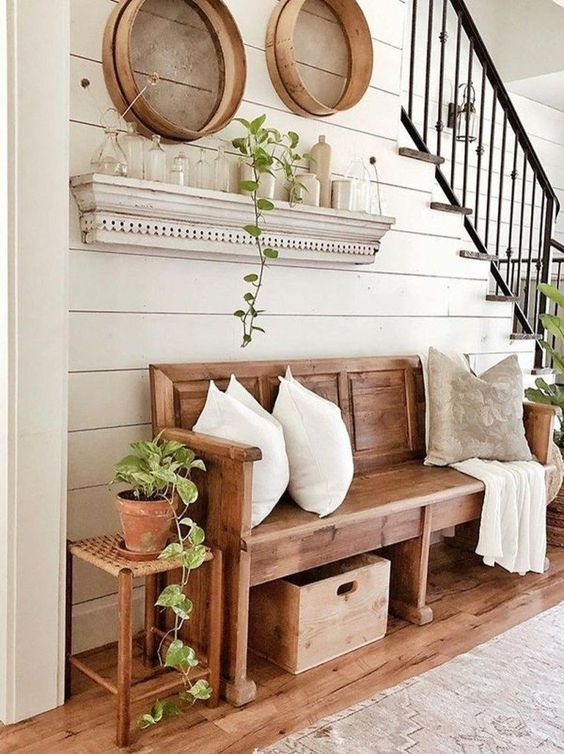 a simple farmhouse entryway with wooden furniture, a box, some wooden trays, greenery and a selection of bottles