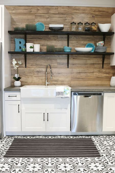 a simple farmhouse kitchen in white with a wooden backsplash and dark open shelving looks catchy and cozy
