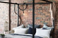 a simple industrial bedroom with red brick walls, a black metal frame bed, wooden and wicker furniture and cozy textiles