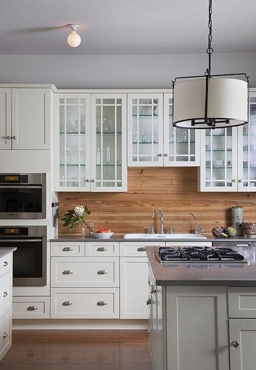 a simple white farmhouse kitchen with elegant cabinets, a wooden backsplash, pendant lamps and a grey kitchen island