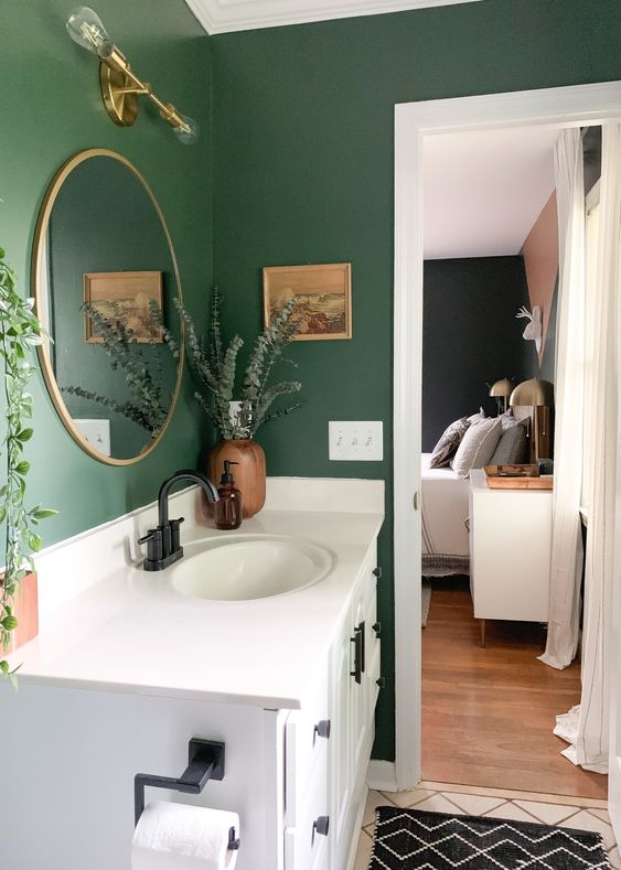 a small bathroom with hunter green walls, a white vanity, printed textiles and greenery in vases and pots