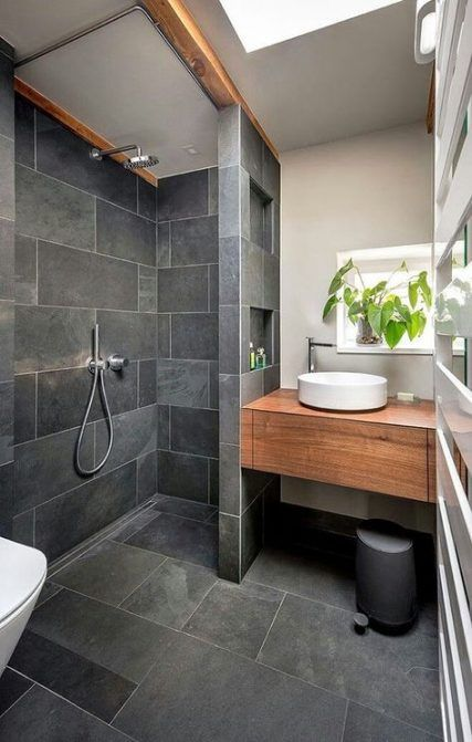 a small grey bathroom clad with tiles, with a built in wooden vanity, white appliances and potted greenery