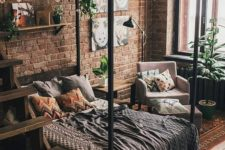 a small yet chic industrial bedroom with red brick walls, a canopy bed, potted greenery and lights plus catchy textiles