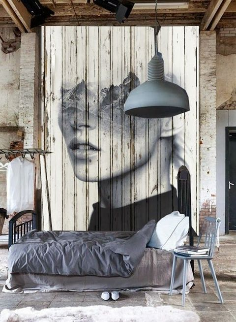 a statement industrial bedroom with brick walls, a large artwork, metal and wood furniture, an open closet and a wood slab ceiling