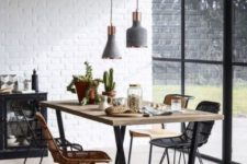 a stylish contemporary dining room with white brick walls, grey and copper lamps, wicker chairs and a glazed wall