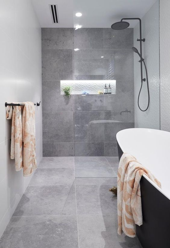 a stylish contemporary grey bathroom clad with large scale tiles, with a lit up niche, a black tub and dark fixtures