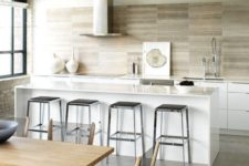a stylish contemporary kitchen with white lower cabinets, black stools, metallic appliances and a wooden backsplash