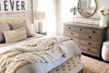 a stylish farmhouse bedroom with neutral walls, rustic vintage furniture, a vintage chandelier and a refined mirror