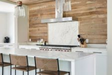 a stylish farmhouse kitchen with white lower cabinets, a marble backsplash and kitchen island, a wooden wall that goes up to the ceiling