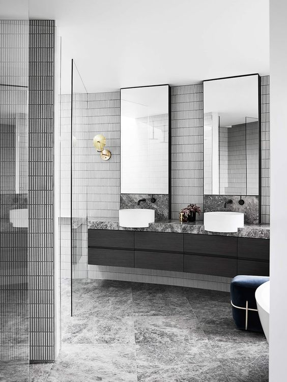 a stylish grey bathroom done with various kinds of tiles, a black floating vanity, two mirrors and sinks and a navy ottoman